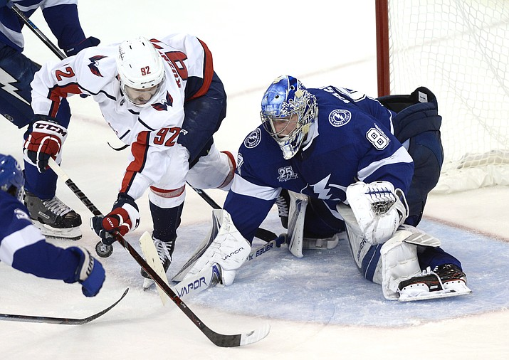 Tampa Bay Lightning goaltender Andrei Vasilevskiy (88) knocks the puck away as Washington Capitals center Evgeny Kuznetsov (92) looks for a shot during the third period of Game 5 of the NHL hockey Eastern Conference finals Saturday, May 19, 2018, in Tampa, Fla. (Jason Behnken/AP)