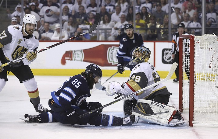 Winnipeg Jets' Mathieu Perreault (85) slides into Vegas Golden Knights goaltender Marc-Andre Fleury (29) during second period NHL Western Conference Finals game 5 hockey action in Winnipeg, Sunday, May 20, 2018. (Trevor Hagan/The Canadian Press via AP)