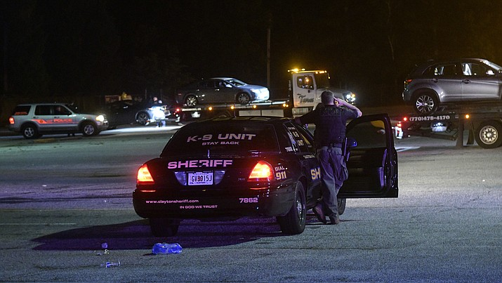 A Clayton County Sheriff's Deputy stands watch over a parking lot at Mt. Zion High School as three cars are towed away as part of an investigation into a fatal shooting Friday, May 18, 2018, in Jonesboro, Ga. One person was killed and another wounded when an argument led to a shooting outside a high school graduation ceremony Friday night in metro Atlanta, police said. The incident happened as people headed to their cars, Clayton County schools' safety chief Thomas Trawick said. (AP Photo/John Amis)