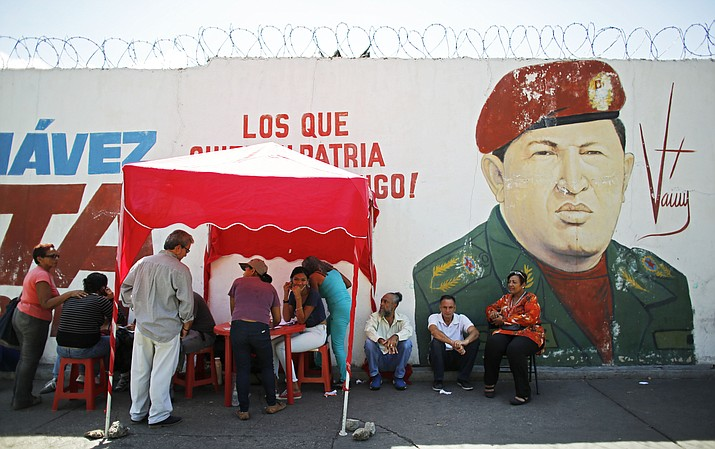 "Voters register with the ruling United Socialist Party after casting their ballots in the presidential election in Caracas, Venezuela, Sunday, May 20, 2018, at a so-called ""red point,"" set up outside a voting center to confirm peoples' cards, which are needed to access government-run social programs. President Nicolas Maduro is seeking a second, six-year term despite a deepening crisis that's made food scarce and inflation soar as oil production in the once-wealthy nation plummets. (AP Photo/Ariana Cubillos)"