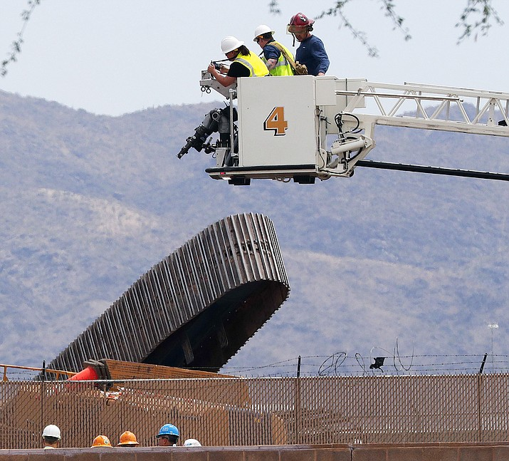 Investigators look down at a toppled crane that was being used in the construction of the Sky Train guideway system at Sky Harbor International Airport Monday, May 21, 2018, in Phoenix. The Phoenix fire department said one person is unaccounted for and their condition is unknown at this time due to the crane being on its side. (AP Photo/Matt York)