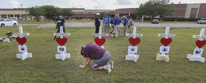 "Santa Fe, Texas, resident, Lori Simmons prays for healing in front of 10 wooden crosses at Santa Fe High School on Monday, May 21, 2018, in Santa Fe. In response to this recent shooting, a ""school liaison officer"" could soon join the Prescott Police Department. The liaison officer would focus mainly on growing concerns about school safety in the community. (Steve Gonzales/Houston Chronicle via AP)"