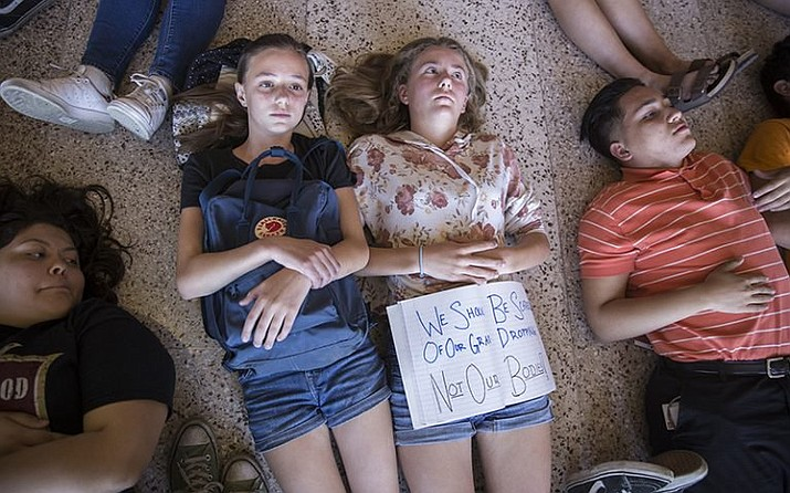 "Sisters Grace, 15, and Imogen, 12, Dietz lie down on the floor of the Senate as part of a protest calling for a dialogue with Republican politicians on gun control in April. The words displayed on the notebook read, ""We should be scared of our grades dropping, not our bodies!"" (Photo by Jenna Miller/Cronkite News)"