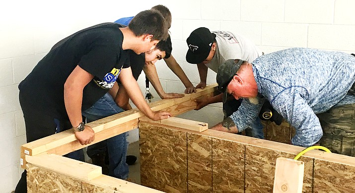 Construction students at Valley Academy of Career and Technology Education build wooden shelving in a recent community service project. (Photo by Bill Helm)