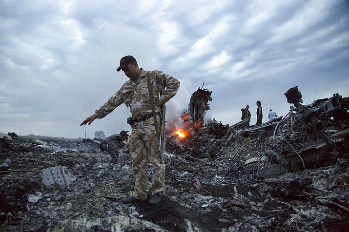 In this July 17, 2014. file photo, people walk amongst the debris at the crash site of a passenger plane near the village of Grabovo, Ukraine. An international team of investigators says that detailed analysis of video images has established that the Buk missile that brought down Malaysia Airlines Flight 17 nearly four years ago came from a Russia-based military unit. Wilbert Paulissen of the Dutch National Police said Thursday, May 24, 2018 that the missile was from the Russian military's 53rd anti-aircraft missile brigade based in the Russian city of Kursk. (AP Photo/Dmitry Lovetsky, File)