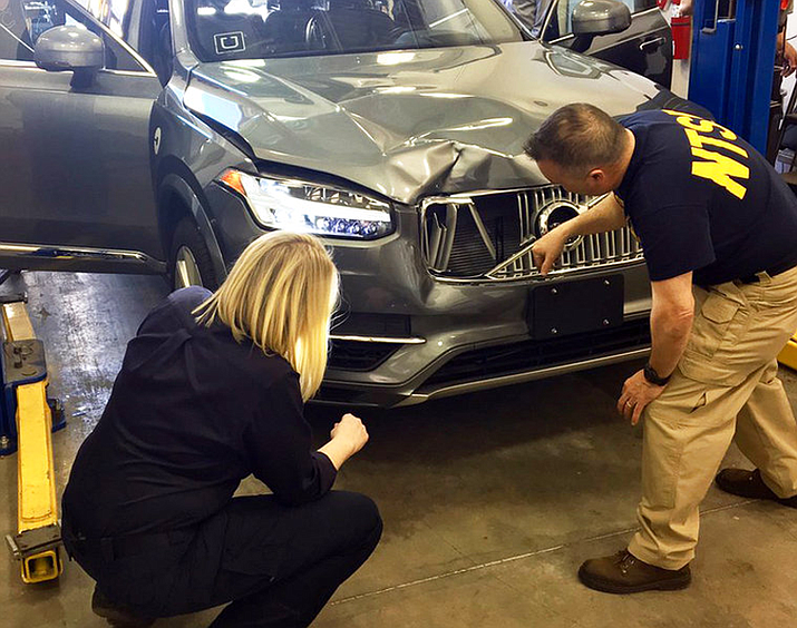 In this March 20, 2018, file photo investigators examine a driverless Uber SUV that fatally struck a woman in Tempe, Ariz. In a preliminary report on the crash released Thursday, May 24, federal investigators said the autonomous Uber SUV that struck and killed an Arizona pedestrian in March spotted the woman about six seconds before hitting her, but didn't stop automatically because emergency braking was disabled. (National Transportation Safety Board via AP, File)
