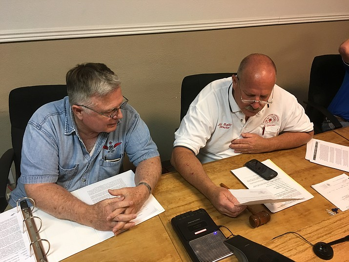 Jim Bailey, right, acting chairman of Northern Arizona Consolidated Fire District board of directors, and newly appointed director Carl Hays look over a scathing letter from Kingman Fire Department on the performance of NACFD Fire Chief Wayne Eder at Wednesday's special meeting. The board voted to fire Eder effective immediately.
