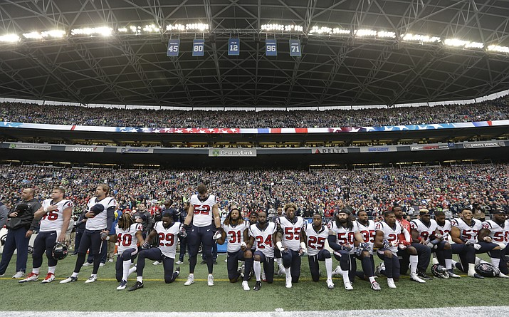 "In this Oct. 29, 2017, file photo, Houston Texans players kneel and stand during the singing of the national anthem before an NFL football game against the Seattle Seahawks, in Seattle. NFL owners have approved a new policy aimed at addressing the firestorm over national anthem protests, permitting players to stay in the locker room during the ""The Star-Spangled Banner"" but requiring them to stand if they come to the field. The decision was announced Wednesday, May 23, 2018, by NFL Commissioner Roger Goodell during the league's spring meeting in Atlanta. (Elaine Thompson/AP, File)"