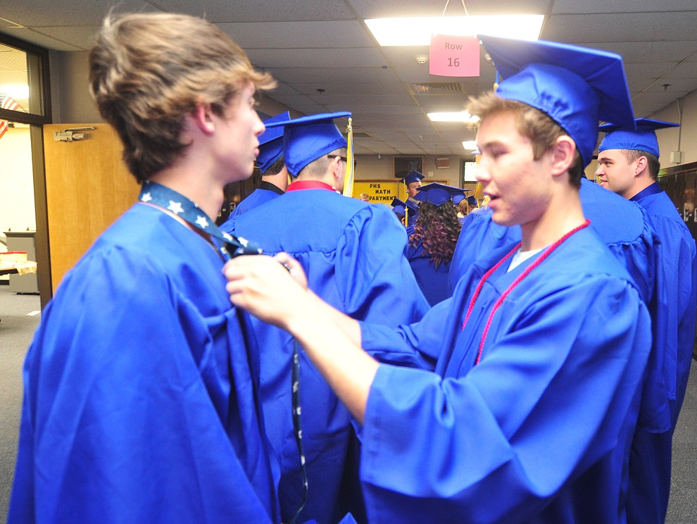 Aaron Martin gets help with his tie from Wyatt Harness before the 2018 Prescott High School Commencement Ceremony at the school Friday, May 25, 2018. (Les Stukenberg/Courier)