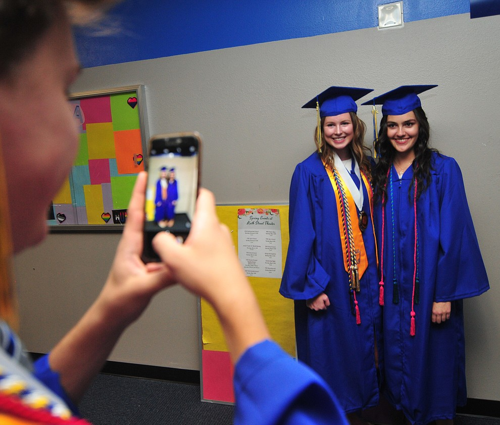 Wesley Bradstreet takes a photo of Lexis Hammes and Mary Powers before the 2018 Prescott High School Commencement Ceremony at the school Friday, May 25, 2018. (Les Stukenberg/Courier)