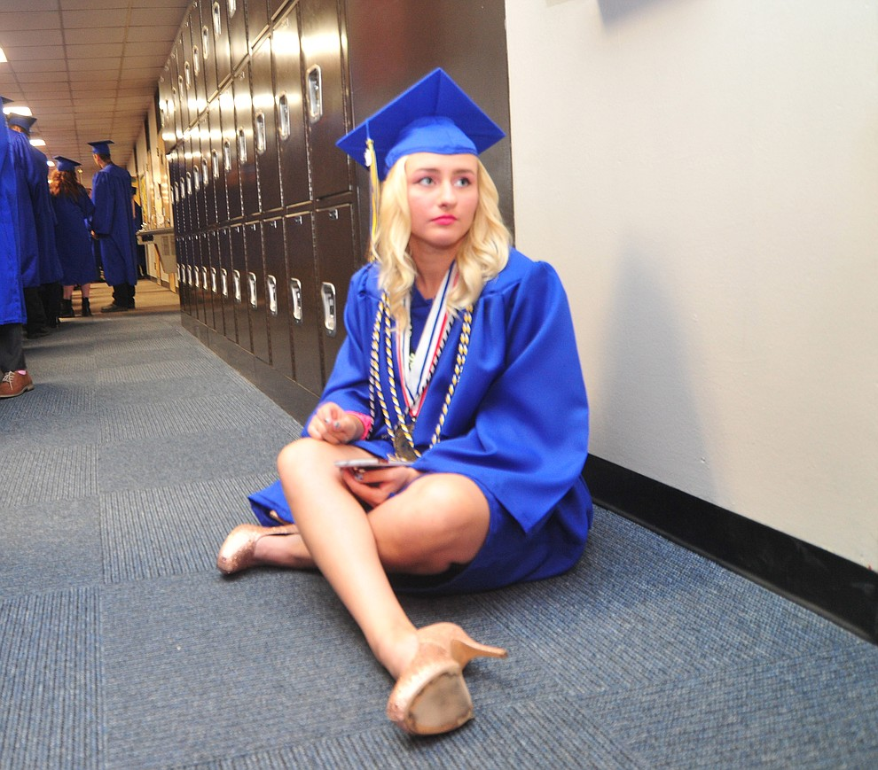 Amanda Hugeri takes a break in the hallway before the 2018 Prescott High School Commencement Ceremony at the school Friday, May 25, 2018. (Les Stukenberg/Courier)