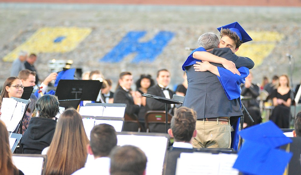 Dan Bradstreet gets a hug from his son Wesley during the 2018 Prescott High School Commencement Ceremony at the school Friday, May 25, 2018. (Les Stukenberg/Courier)