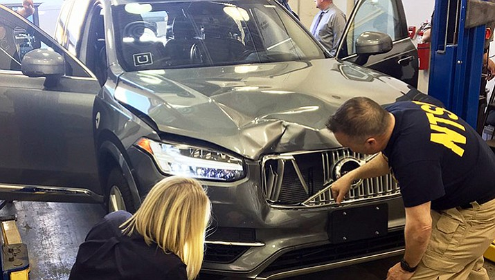 In this March 20, 2018, file photo provided by the National Transportation Safety Board, investigators examine a driverless Uber SUV that fatally struck a woman in Tempe, Ariz. In a preliminary report on the crash released Thursday, May 24, federal investigators said the autonomous Uber SUV that struck and killed an Arizona pedestrian in March spotted the woman about six seconds before hitting her, but didn't stop automatically because emergency braking was disabled. (National Transportation Safety Board)