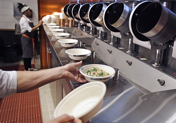 "A worker lifts a lunch bowl off the production line at Spyce, a restaurant which uses a robotic cooking process, in Boston, Thursday, May 3, 2018. Robots can't yet bake a souffle or fold a burrito, but the new restaurant in Boston is employing what it calls a ""never-before-seen robotic kitchen"" to cook up ingredients and spout them into a bowl. (Charles Krupa/AP, file)"