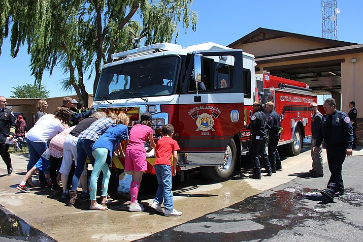 Central Arizona Fire and Medical Authority personnel and their family members participate in a fire engine dedication ceremony in Dewey on Thursday, May 24. The ceremony recognized the replacement of Station 54's fire engine with a new fire engine and included pushing the new fire engine into its quarters for its first time in service. (Max Efrein/Courier)