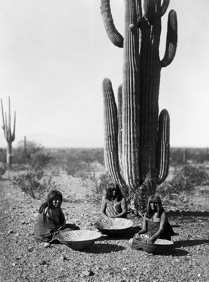 Three Maricopa women with baskets, seated in front of a Saguaro cacti in southern Arizona.
