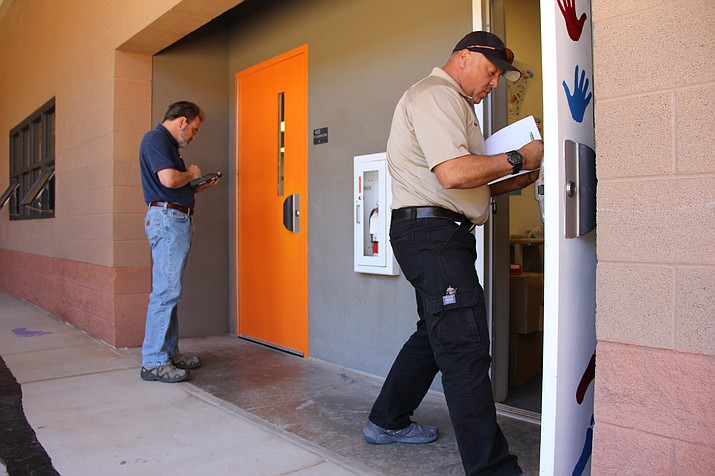 Tom Foley (left), Embry-Riddle Aeronautical University's assistant professor of global security and intelligence, and Richard Rodriguez, study the doors at Bright Futures Pre-school in Prescott Valley for a study their conducting on school safety. (Max Efrein/Courier)