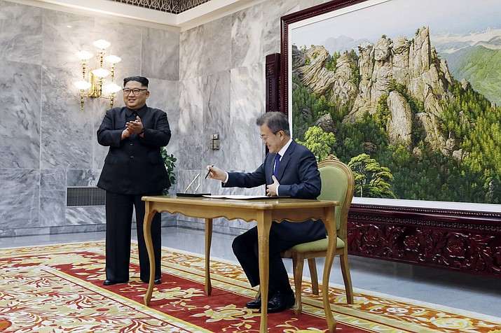 In this May 26, 2018 photo provided on May 27, 2018, by South Korea Presidential Blue House, South Korean President Moon Jae-in writes on a visitor's book as North Korean leader Kim Jong Un, left, stands at the northern side of Panmunjom in North Korea. Kim and Moon met Saturday, May 26 for the second time in a month, exchanging a huge bear hug and broad smiles in a surprise summit at a border village to discuss Kim's potential meeting with U.S. President Donald Trump and ways to follow through on the peace initiatives of the rivals' earlier summit. (South Korea Presidential Blue House)
