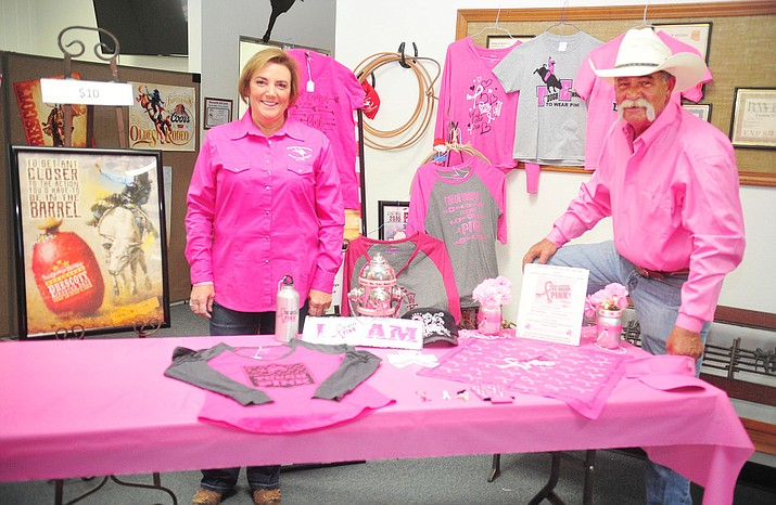 """Tough Enough to Wear Pink Chairwoman Denine Graff and her husband, Prescott Frontier Days President Chris Graff, pose in the rodeo office with some of the merchandise used to raise money for the fight against breast cancer. People who are """"tough enough to wear pink"""" in rodeo cowboy country will prove the strength of their mettle at a dinner on June 2 to raise money for the fight against breast cancer. July 2 is Tough Enough to Wear Pink night at the Prescott Frontier Days Rodeo. (Les Stukenberg/Review)"""