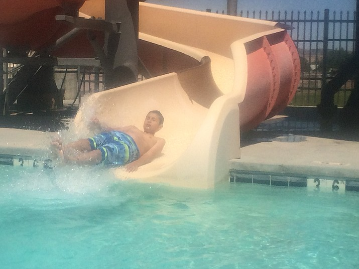 Dean Gaskill shoots out of the water slide at the Chino Valley Aquatic Center on opening day Friday, May 25. The Chino Valley Aquatic Center is located at 1615 N. Road 1 East. For more information, call 928-636-9780. (Jason Wheeler/Review)