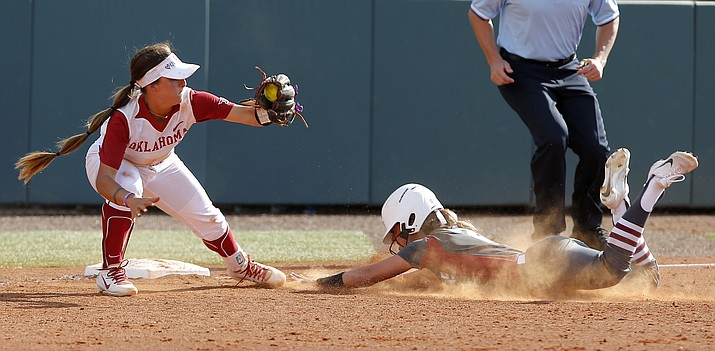 Arkansas' Sydney Parr slides into second as Oklahoma's Sydney Romero (2) catches the throw during the seventh inning during the first game of an NCAA softball super regional in Norman, Okla., Friday, May 25, 2018. (Sarah Phipps/The Oklahoman via AP)