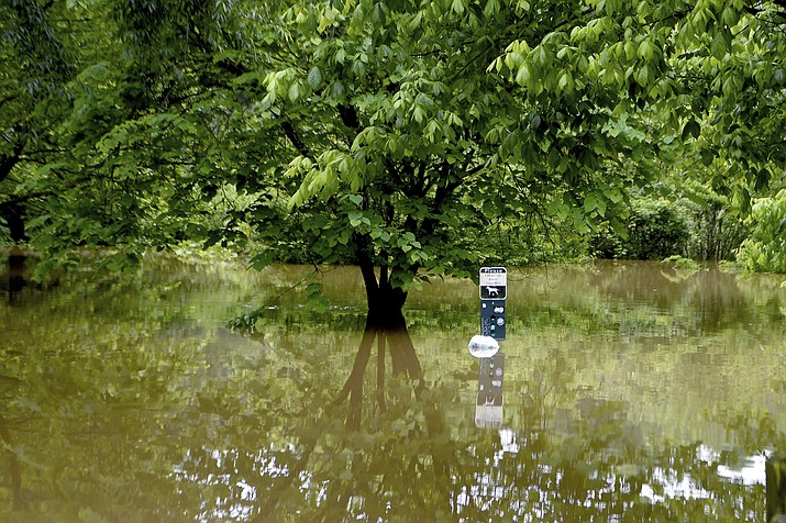 A sign sticks out of the water from the French Broad River that flooded into Carrier Park in Asheville, N.C., Wednesday, May 30, 2018. The soggy remnants of Alberto spread rain deeper into the nation's midsection after downing trees, triggering power outages and scattering flooding around the South. (Angeli Wright /The Asheville Citizen-Times via AP)