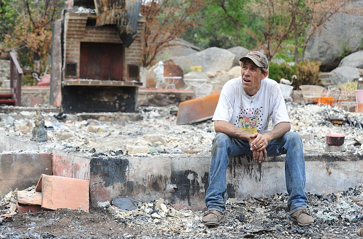 Joe Tyree takes a break from the cleanup of a burned home in Yarnell on July 23, 2013. Suggestions are coming in for memorializing the Granite Mountain Hotshots who died fighting the Yarnell Hill fire on June 30, 2013. (Les Stukenberg/ Courier file)