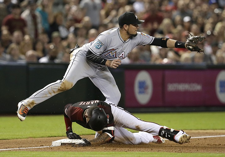Arizona Diamondbacks' Ketel Marte (4) slides into third base safely with an RBI triple under the tag of Miami Marlins third baseman Miguel Rojas during the second inning of a baseball game Saturday, June 2, 2018, in Phoenix. (AP Photo/Rick Scuteri)