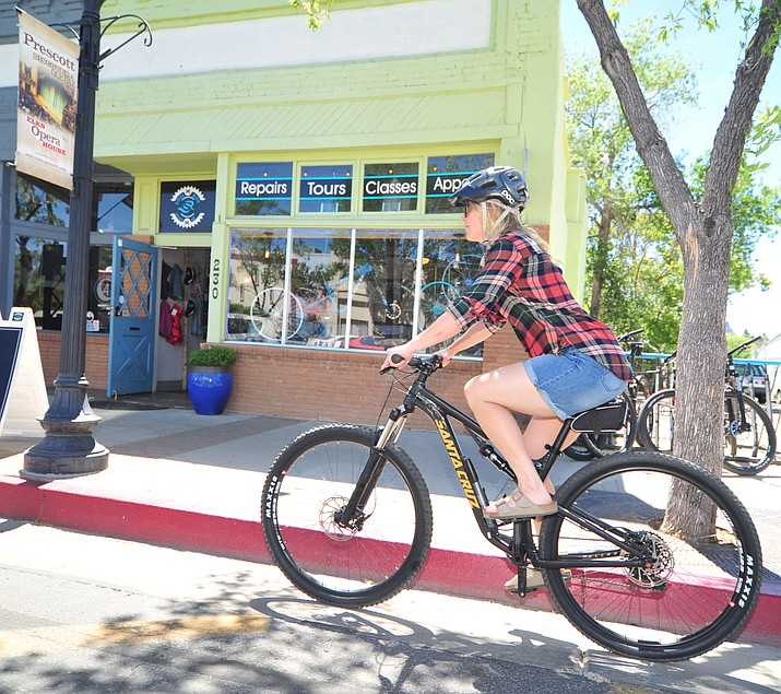 Co-owner Kate Phelan rides a demo bike in front of Soul Ride on Montezuma Street in Prescott Thursday, May 31, 2018. (Les Stukenberg/Courier)