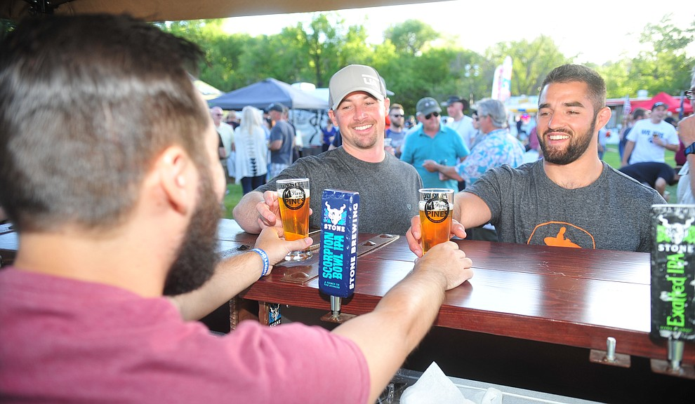 Stone Brewing's Dane Barber serves Cody Alexander and Sam Shapiro at Prescott Area Young Professionals 8th annual Party in the Pines at Prescott Mile High Middle School in Prescott Saturday, June 2, 2018. (Les Stukenberg/Courier, file)
