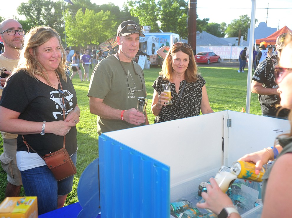 Beth Mull, Rick and Lori Kelley wait for a beer at Goldenrod Brewing's booth at Prescott Area Young Professionals 8th annual Party in the Pines at Prescott Mile High Middle School in Prescott Saturday, June 2, 2018. (Les Stukenberg/Courier)