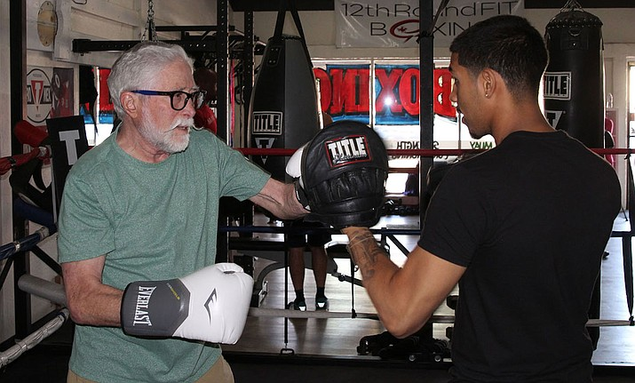 Sheldon Nitzay, left, spars with boxing trainer Isaiah Flores. In addition to boxing three days per week, Nitzay says he also tap dances to curb symptoms of Parkinson's.