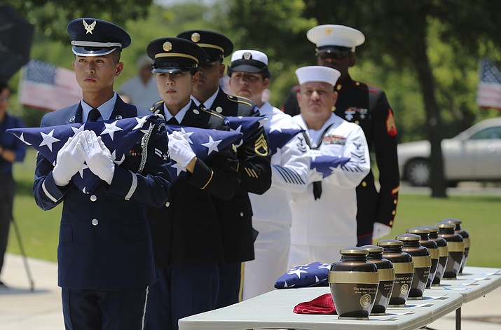 In this Friday, June 1, 2018 photo, military service members with the Armed Services Honor Guard prepare to present folded flags as Fort Sam Houston National Cemetery and the Missing in America Project conduct a military burial service for the cremated remains of eight unclaimed veterans in San Antonio. The remains of eight U.S. military veterans that for years had been stored in the basement of a county courthouse in the Texas Panhandle have been interred as part of a formal ceremony in San Antonio. (Kin Man Hui/The San Antonio Express-News via AP)