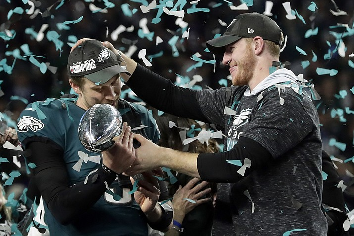 Philadelphia Eagles quarterback Carson Wentz, right, hands the Vincent Lombardi trophy to Nick Foles after winning the NFL Super Bowl 52 football game against the New England Patriots in Minneapolis on Feb. 4, 2018. The Eagles won 41-33.  (AP Photo/Frank Franklin II, file)