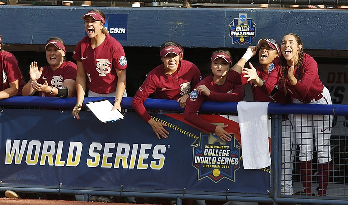 Florida State players cheer in the dugout in the second inning of the first softball game of the best-of-three championship series against Washington in the NCAA Women's College World Series in Oklahoma City, Monday, June 4, 2018. (AP Photo/Sue Ogrocki)