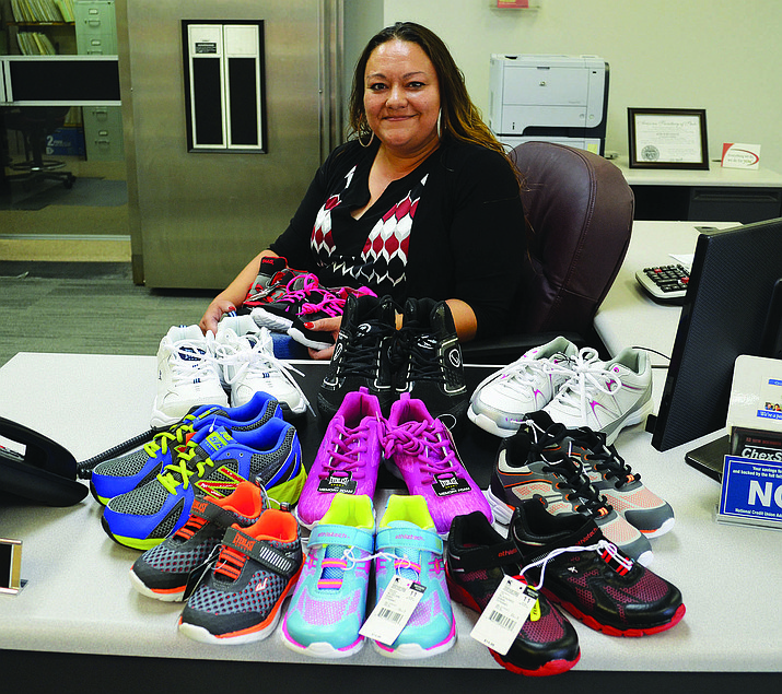 Mohave Community Federal Credit Union employee and Kicks for Kids organizer Ramona Baptista poses with shoes collected from the drive in 2016. (Daily Miner file photo)