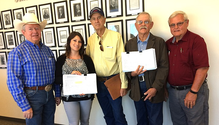 Jenn Nelson of the Yavapai County School Superintendent's Office accepts petitions Monday morning from members of the Committee for Better Upper Verde Valley Schools  to have the school district consolidation question placed on the November 2018 ballot. From left, Andy Groseta, Nelson, Jerry Brown, Bob DeGeer and Phil Terbell. They submitted petitions with 2,312 voter signatures requesting consolidation be placed on the ballot. (Photo by Nanci Hutson)
