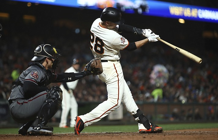 San Francisco Giants' Buster Posey swings for a two RBI double off Arizona Diamondbacks' Fernando Salas in the fourth inning of a baseball game Monday, June 4, 2018, in San Francisco. (AP Photo/Ben Margot)