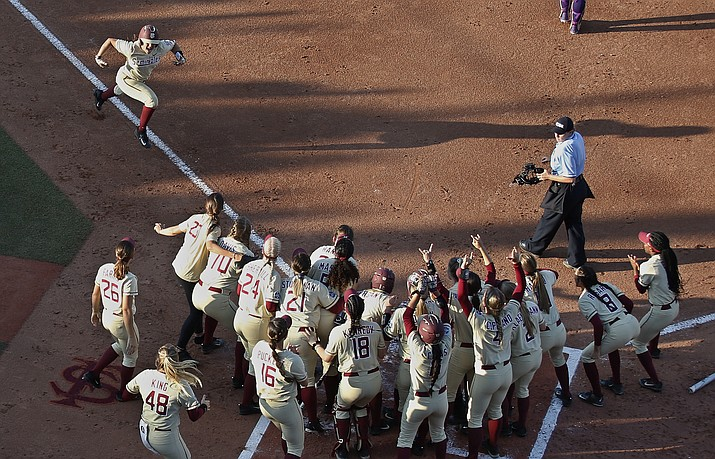 Florida State catcher Anna Shelnutt (13) celebrates her home run as she runs toward her teammates waiting at home plate in the first inning of the second game of the best-of-three championship series against Washington in the NCAA softball  Women's College World Series in Oklahoma City, Tuesday, June 5, 2018. (AP Photo/Sue Ogrocki)