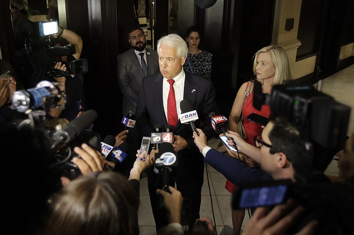 Republican gubernatorial candidate John Cox, center, speaks to reporters alongside his wife, Sarah Cox, right, Tuesday, June 5, 2018, in San Diego. The intrigue in the race to replace departing California Gov. Jerry Brown isn't who wins — it's who comes in second in Tuesday's primary, one of hundreds of contests across the state that could solidify Democratic dominance and reshape the fight for control of the U.S. Congress. (AP Photo/Gregory Bull)