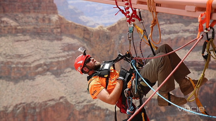 Cleaners use a variety of ropes, pulleys and ties to position themselves below the glass walkway. (Photo/Abseilon USA)