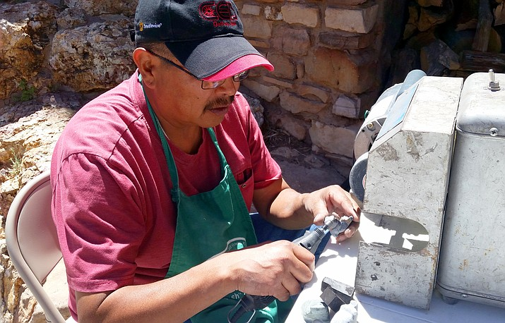 Zuni fetish carver Mike Tucson carves a piece of jet that will become a wolf. (Erin Ford/WGCN)