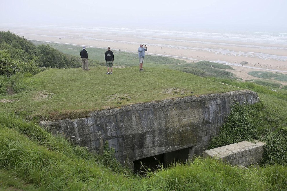 US Tourists have a look at Omaha beach next to the Colleville American military cemetery, in Colleville sur Mer, western France, Wednesday June 6, 2018, on the 74th anniversary of the D-Day landing. U.S. and other allied troops have joined veterans of the D-Day invasion and families of fallen soldiers to mark 74 years since the massive military operation that change the course of World War II. (AP Photo/David Vincent)