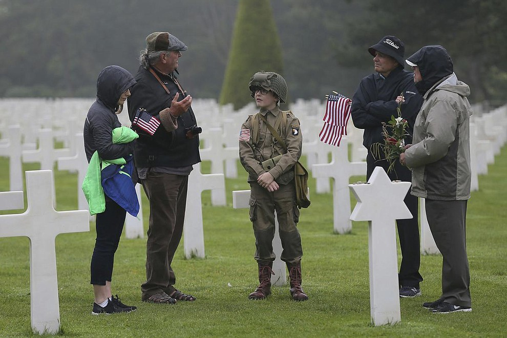 David Chamberlain, second right and his family, from left to right, his wife June, his son Steve, center, and grandfather Charly Powers, from Atlanta, Georgia, visit the Colleville American military cemetery, in Colleville sur Mer, western France, Wednesday June 6, 2018, on the 74th anniversary of the D-Day landing. U.S. and other allied troops have joined veterans of the D-Day invasion and families of fallen soldiers to mark 74 years since the massive military operation that change the course of World War II. (AP Photo/David Vincent)