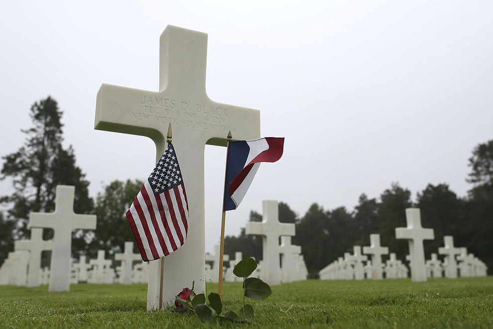 US and French flags and a flower are placed on the grave ofJames D. Black, from New York, who died on June 11, 1944, at the Colleville American military cemetery, in Colleville sur Mer, western France, Wednesday June 6, 2018, on the 74th anniversary of the D-Day landing. (AP Photo/David Vincent)