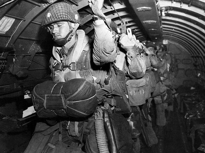 In this photo provided by the U.S. Army Signal Corps, U.S. paratroopers fix their static lines before a jump before dawn over Normandy on D-Day June 6, 1944, in France. The decision to launch the airborne attack in darkness instead of waiting for first light was probably one of the few Allied missteps on June 6, and there was much to criticize both in the training and equipment given to paratroopers and glider-borne troops of the 82nd and 101st airborne divisions. Improvements were called for after the invasion; the hard-won knowledge would be used to advantage later. (AP Photo/U.S. Army Signal Corps)