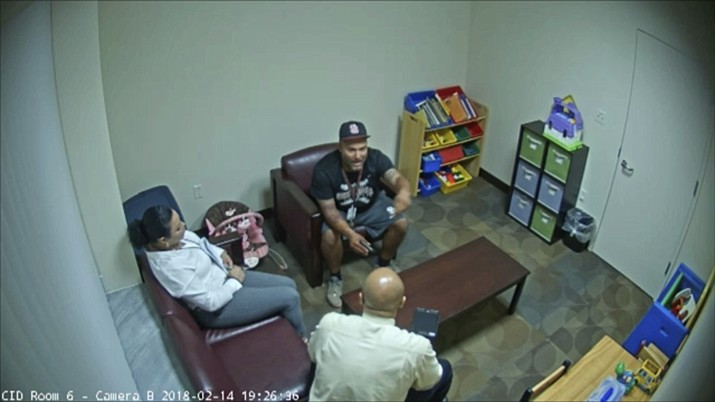 In this Feb. 14, 2018 frame from surveillance video provided by the Broward Sheriff's Office, Andrew Medina, center, is interviewed by detectives following the shooting at Marjory Stoneman Douglas High School in Florida. Medina, a baseball coach and unarmed campus monitor, told detectives he watched Nikolas Cruz get out of an Uber and head straight to the building where 17 people would be killed moments later at the school. (Broward Sheriff's Office)