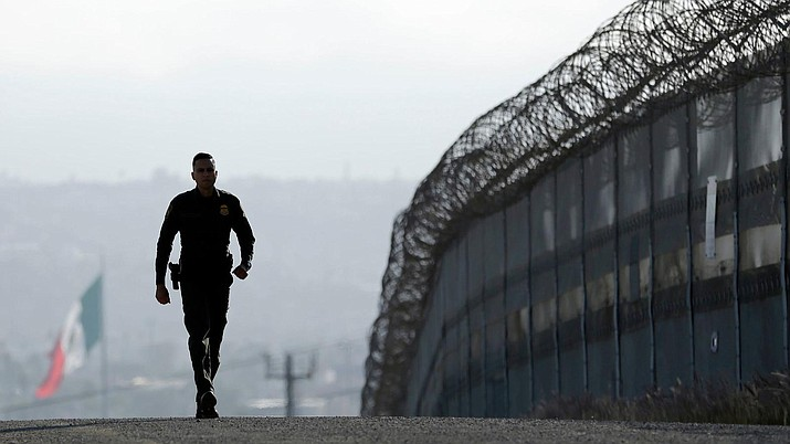 In this file photo Border Patrol agent Eduardo Olmos walks near the secondary fence separating Tijuana, Mexico, and San Diego in 2016. (Gregory Bull/AP File)