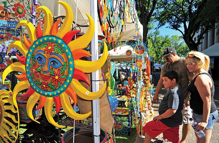 Michael Monroe, his son Dominic, 7, and Leslie Mundell of Prescott Valley check out some of the metal works, pottery, and tables made by Connie Adams of Scottsdale Saturday afternoon at the courthouse plaza during the Prescott Territorial Days Arts & Crafts show. (Kudos file photo)