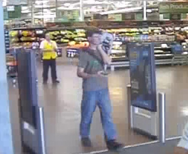 Police originally released a photo of a young man they called a person of interest who was seen on store surveillance exiting the store Tuesday, June 5, 2018. In the surveillance images police said he appeared to take the case. But in a later statement police said detectives were able to identify the young man and that he was cooperating with investigators.  (Kingman Police Department)